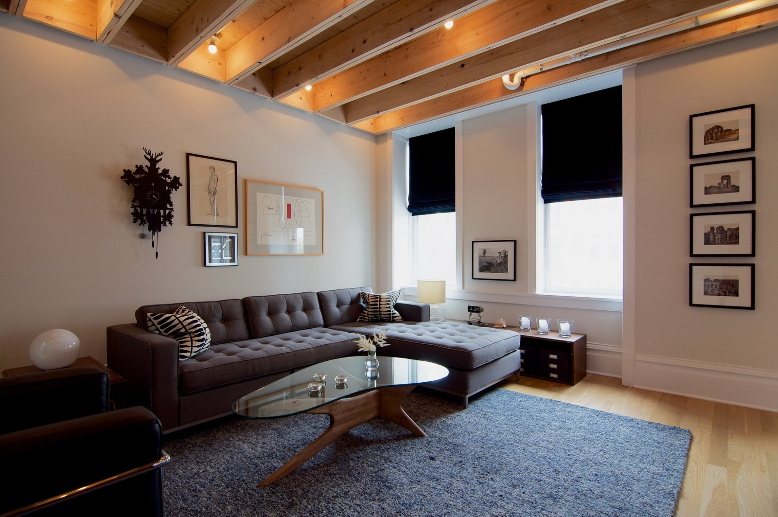 """It was a design priority that any modern interventions had an articulate edge or gap against the existing space,"" says Shively. As a result, he designed a subtle gap between the exposed beam ceiling and the existing walls. The living room also features a Gus* Modern sofa and Adrian Pearsall coffee table. A Chicago Renovation Taps Into its Attic to Almost Double its Square Footage - Photo 5 of 8"