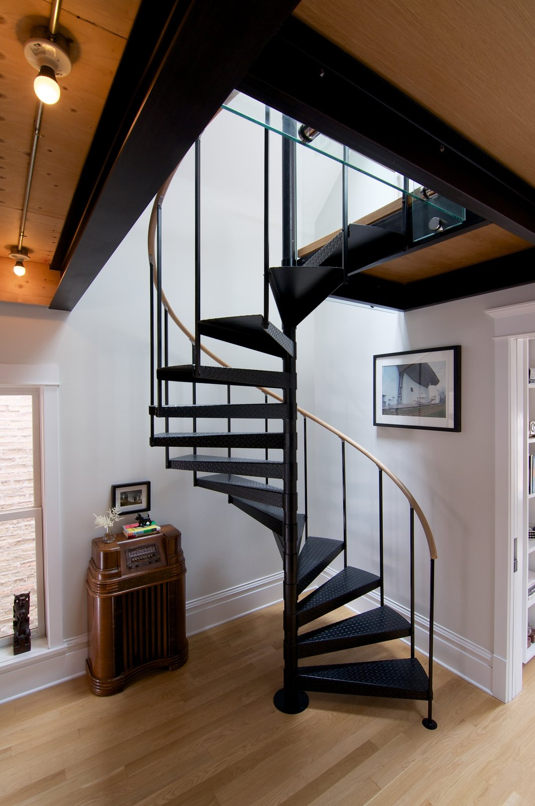 Shively had a carpenter from TomKal Construction build a custom handrail, out of white oak to match his floors, for this spiral staircase. A Chicago Renovation Taps Into its Attic to Almost Double its Square Footage - Photo 6 of 8