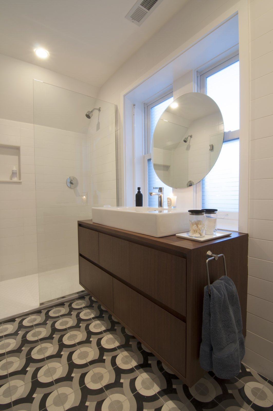 "Shively describes himself as ""big on graphics"" and designed these tiles, produced by Original Mission Tile in San Luis, Mexico, to add his own flair to the master bathroom. A simple floating vanity and minimalist shower let the custom tilework take center stage."