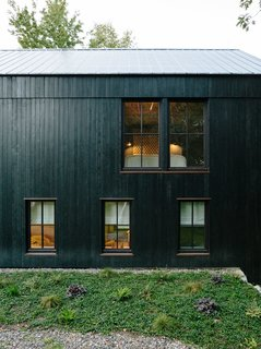 The main house is constructed from structural insulated panels from Vermont Timber Frames and clad in charred cedar. The roof panels are by Agway Metals.