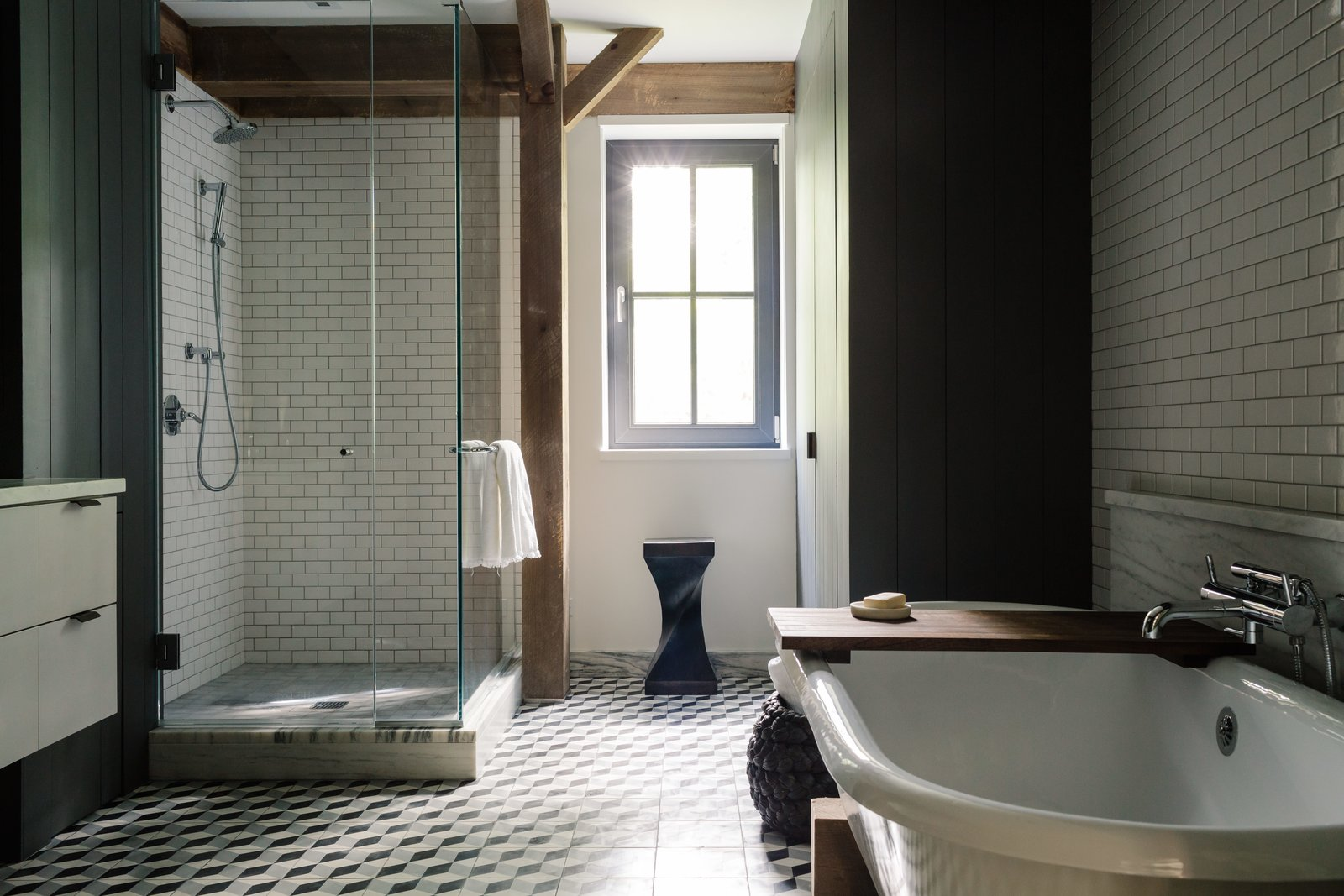 "In the master bathroom, the cement floor tiles are by Mosaic House; the glazed subway tiles are from Daltile; and the trim is honed, vein-cut Montclair Danby marble. The Signature Hardware tub sits in a custom wood cradle designed to match the home's timber frame; the fixtures are by Waterworks. The Twist stool is from Classic Country in nearby Hudson, New York. Tagged: Bath Room, Subway Tile Wall, Cement Tile Floor, Freestanding Tub, and Corner Shower.  Photo 7 of 13 in A Passive House and ""Sauna Tower"" Join a 19th-Century Barn in the Hudson Valley"