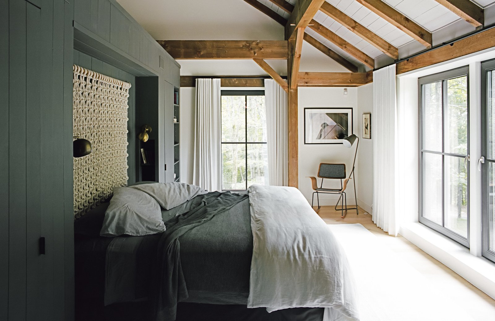 "The bedding is intentionally simple, without layers of unnecessary pillows, and the ""non-headboard headboard,"" as Santos describes it, is a loose macramé wall hanging by Sally England. The built-in storage wall that defines the space is painted Kendall Charcoal by Benjamin Moore in a matte finish—a shade used on millwork throughout the house. The Isaac brass sconces are from Schoolhouse Electric, and the floor lamp is from Crate & Barrel. The rocker was custom made by Onefortythree in Las Vegas. Tagged: Bedroom, Bed, Chair, Lamps, and Light Hardwood Floor.  Photo 4 of 13 in A Passive House and ""Sauna Tower"" Join a 19th-Century Barn in the Hudson Valley"