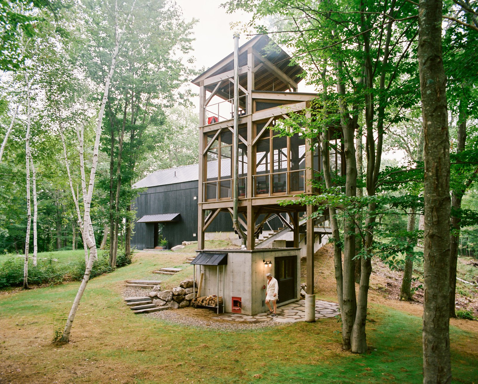 Connected to the main house by a narrow bridge, a three-story cedar tower with a sauna at its base recalls a tree house. The screened-in second level includes a table and chairs for enjoying an outdoor meal, while a swing on the tower's top level provides a perch to take in the surrounding birch trees.