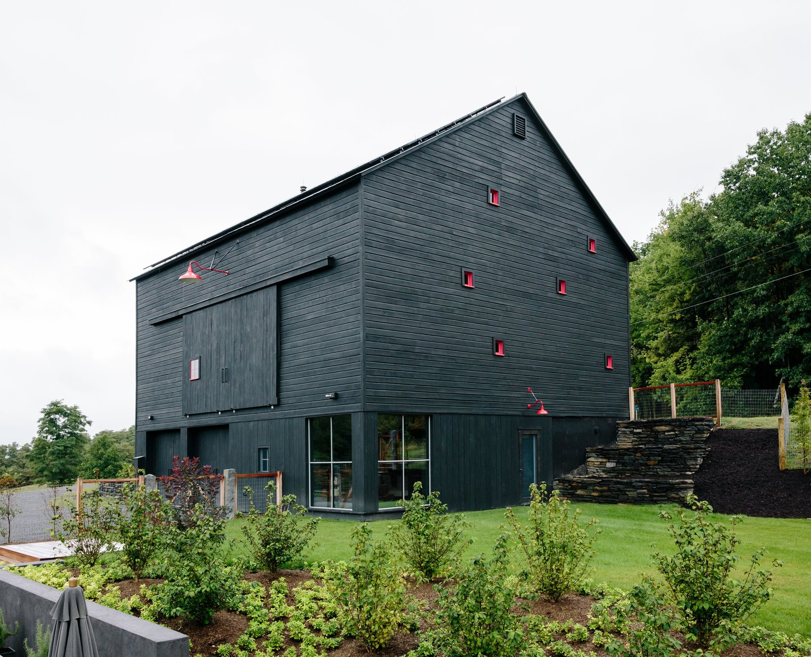 "While the house is a private sanctuary, the barn is a gathering place, especially in summer. On its lower level, a studio apartment recalls the main house with its Intus windows oriented to maximize solar gain. Tagged: Gardens, Grass, Exterior, Wood Siding Material, and House.  Photo 6 of 13 in A Passive House and ""Sauna Tower"" Join a 19th-Century Barn in the Hudson Valley"