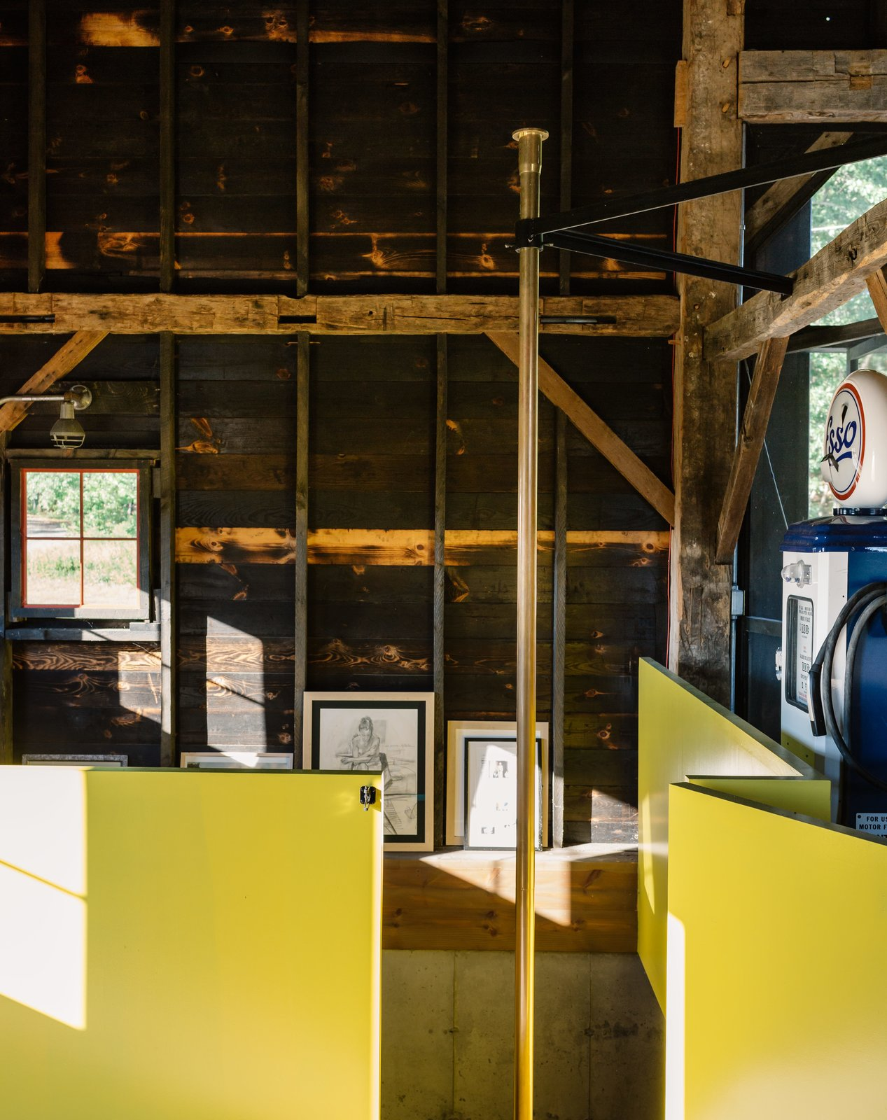 "The contractor sourced the brass pole from a fire station in Boston. The surrounding wall is painted in semi-gloss paint in Citrus by Sherwin Williams, a sunny hue the team playfully referred to as Dwell-ow. Tagged: Shed & Studio and Den.  Photo 9 of 13 in A Passive House and ""Sauna Tower"" Join a 19th-Century Barn in the Hudson Valley"
