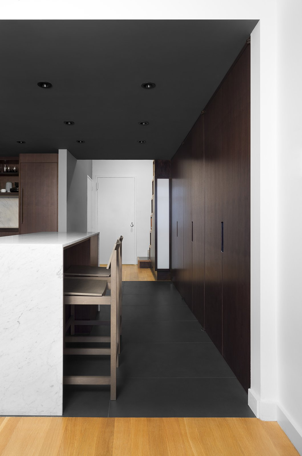 "Zames reconfigured the apartment to improve circulation and open some of the confined rooms. What was formerly a hallway is now integrated with the kitchen. A bank of floor-to-ceiling cabinets offers storage and an island covered in carrara marble offers space for working or dining. ""We embraced dark colors in the kitchen to keep a contrast with the bright white of the surrounding living areas,"" Zames says of the constrasting finishes. The barstools are from CB2."