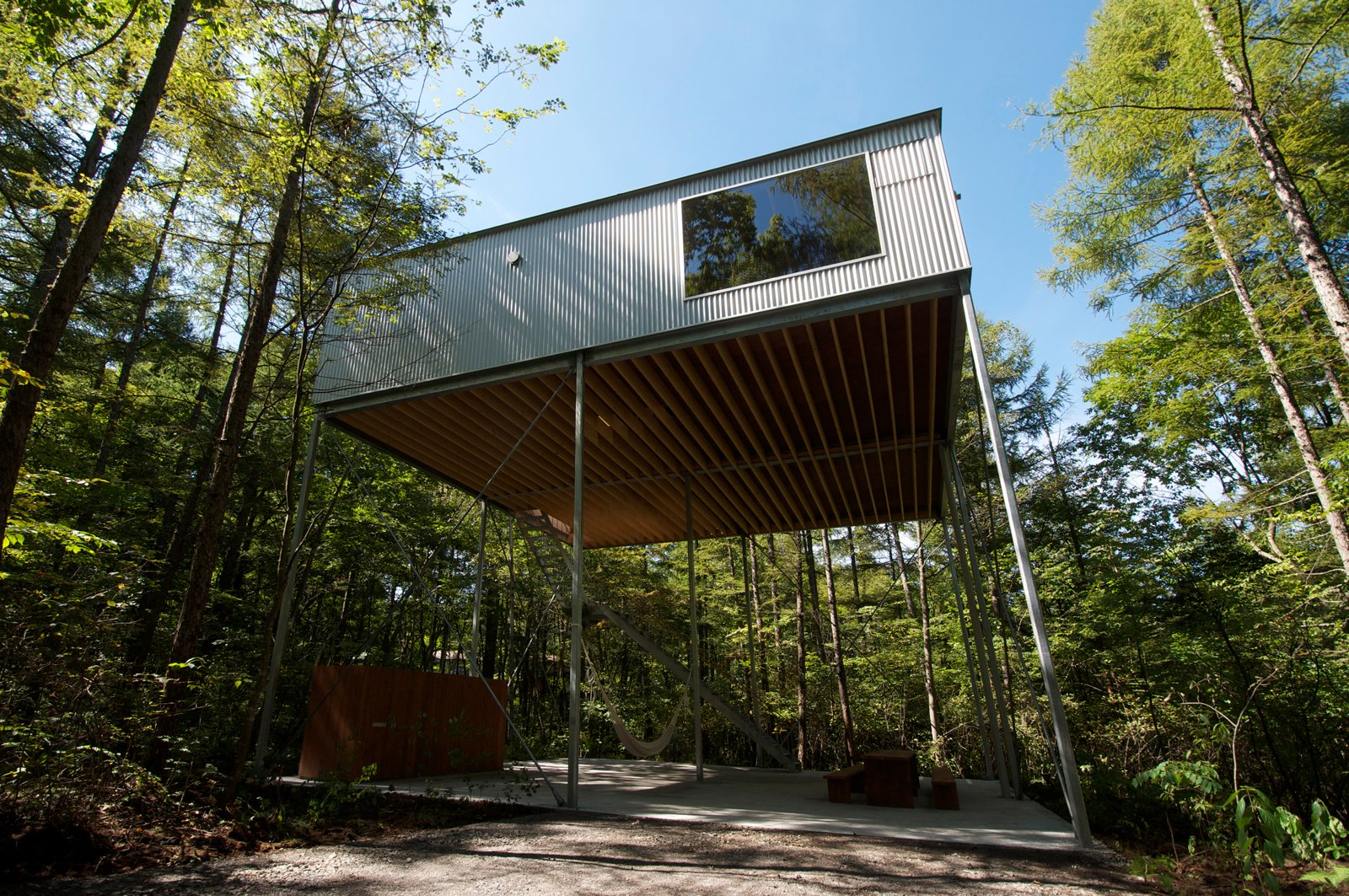 Nine slender, 100 x 100 millimeter square steel columns that are held in place by crossed braces on all four sides hold the small weekend house 6.5 meters in midair. Modern Treehouses by Aileen Kwun