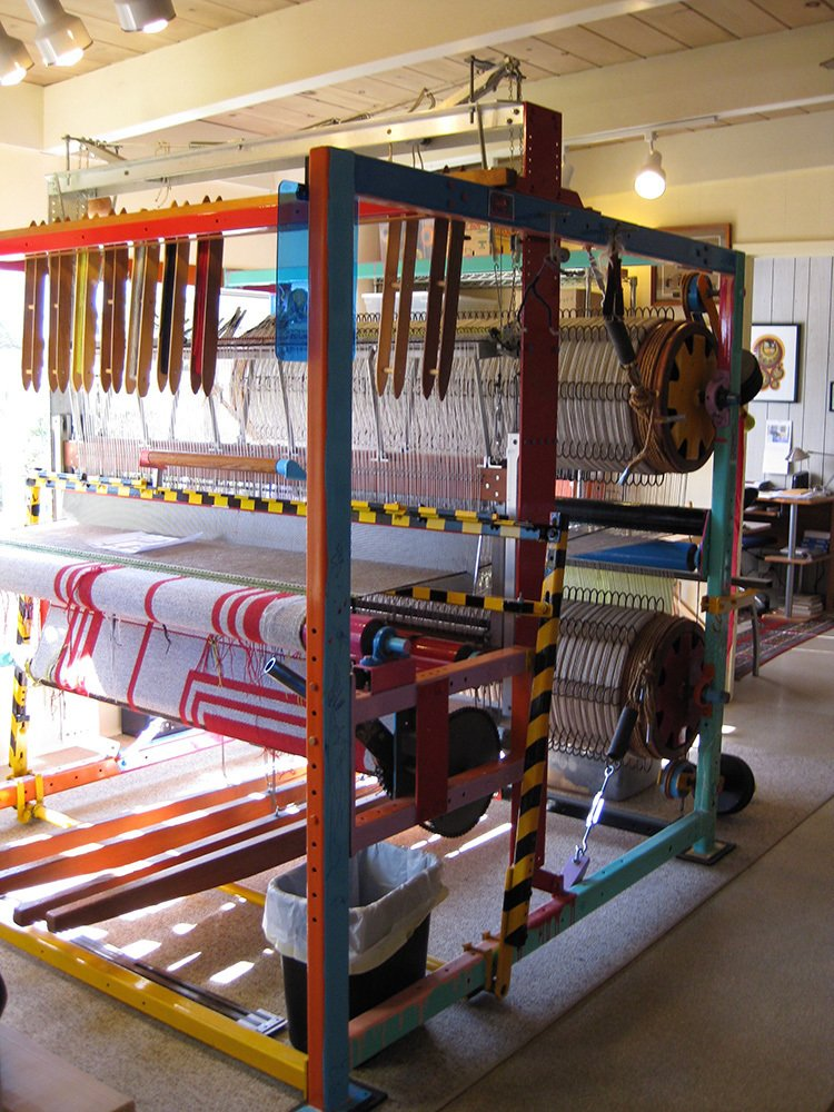 "What's it like to work with this piece of machinery?  ""The loom can be very cantankerous and I have had to learn a few mechanical tricks to keep it in good repair. There are parts that are rigged with aircraft cable and it eventually breaks and needs to be replaced, sometimes mid-project. The brake mechanism consists of heavy rope, springs, turnbuckles, and bar-bell weights that hang from arms on the two large back beams. It is all mechanical, nothing automated. Some have asked me if it is some kind of work-out machine.""  This American Maker Uses a Custom, Artist-Designed Loom to Create Geometric Textiles by Heather Corcoran"
