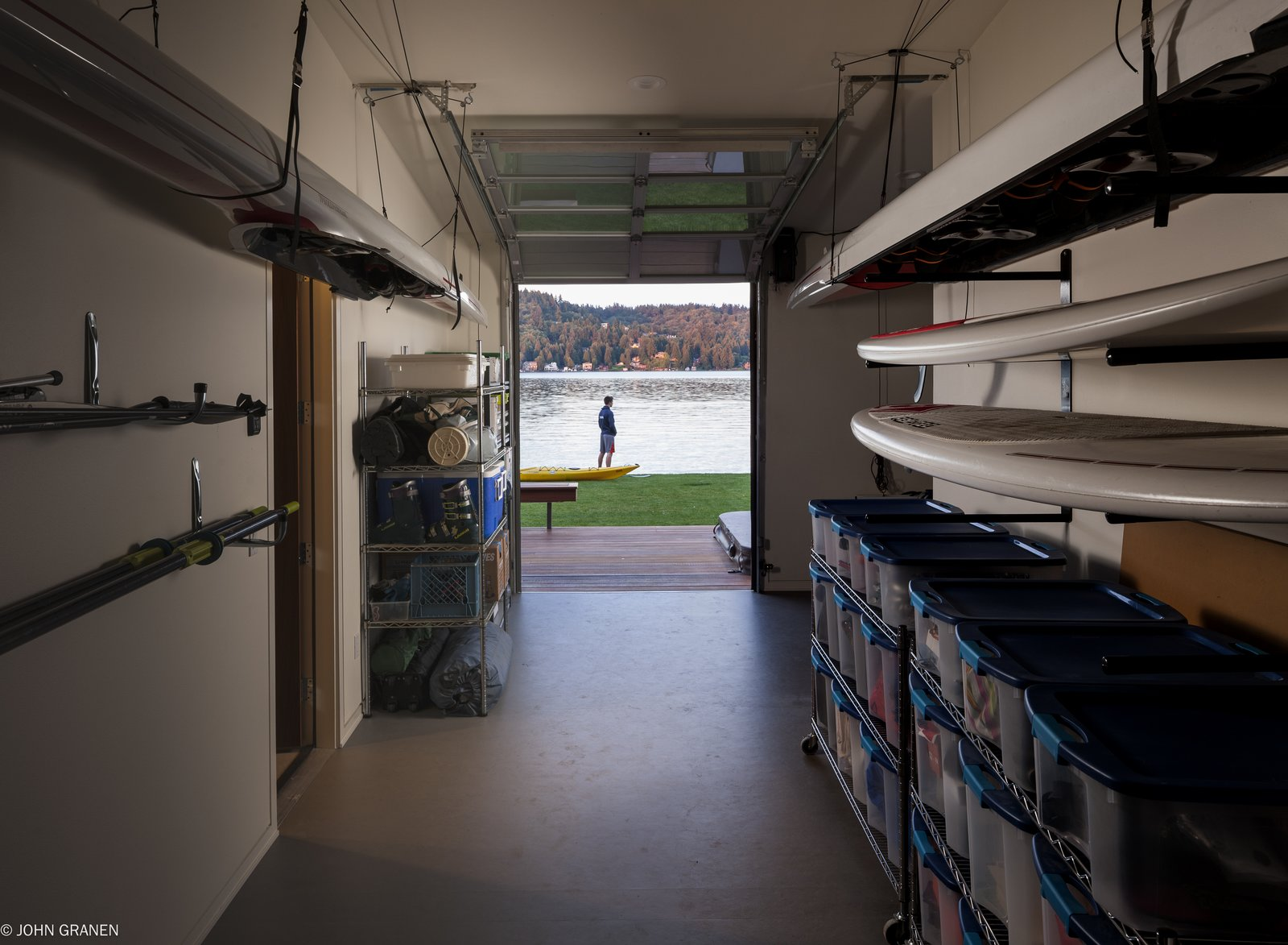 """""""They are a very active family, with rowing and basketball at the top of the list,"""" Witt says. """"Other activities include water sports, volleyball, and entertaining—even in the winter months, which have short, usually damp days."""" Witt created a garage deep enough to hang rowing shelves and enclosed it in a Wayne Dalton garage door.  Garage by Jonathan Minori from A Richly Detailed Seattle Home Built Around a Family's Active Lifestyle"""