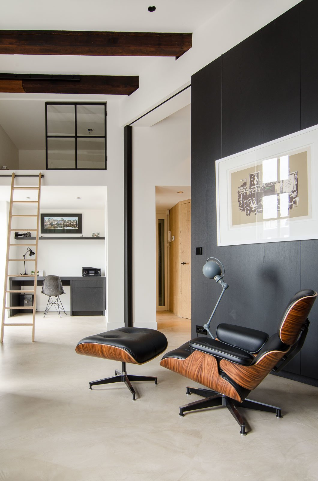 This open-concept Amsterdam loft features soaring 15-foot ceilings, an Eames lounge chair and ottoman, and a Jielde light. Throughout the home, Standard Studio architects Wouter Slot and Jurjen van Hulzen favored raw materials, including concrete, oiled oak, and hot-rolled steel, all of which complemented the original space's industrial feel. Tucked smartly underneath the loft, a compact home office features functional built-in shelving and an Eames DSR chair. Tagged: Living Room, Concrete Floor, Recliner, and Chair.  Loft by Tremaine Eppenger from Bloemgracht