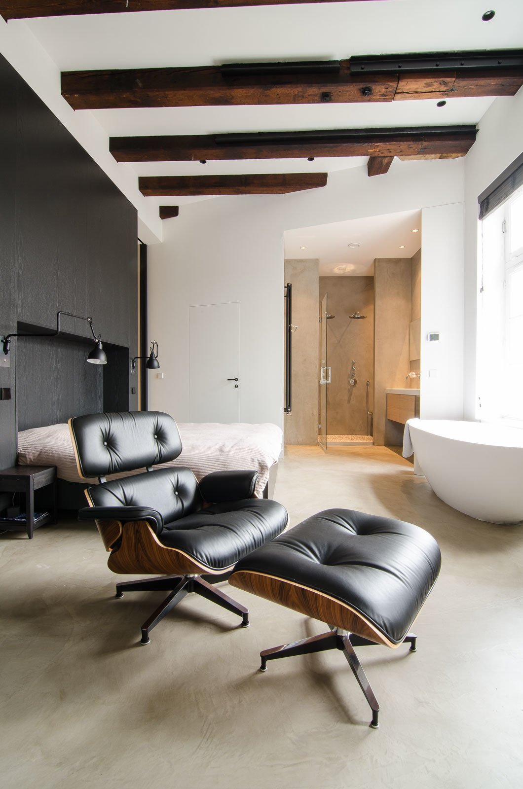 "When planning the renovation, the owner gave Standard Studio complete freedom to develop the design. In the unconventional bedroom, the bed sits against a black feature wall, with a prominent freestanding bathtub on the opposite side. In addition to the wood beams, all original windows from the old sugar refinery were preserved, to keep the ""soul"" of the building intact.  Loft by Daniel Lozada from Bloemgracht"