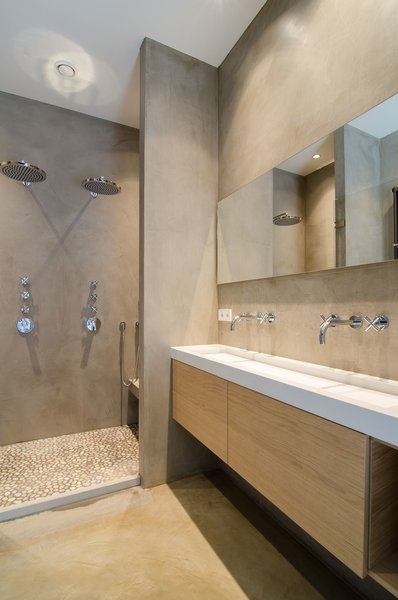 Adjacent to the bedroom, the bathroom features microcement-coated walls, along with a custom sink and vanity. Dornbracht Tara sink faucets and dual rainfall showerheads finish the space. Photo 4 of Bloemgracht modern home
