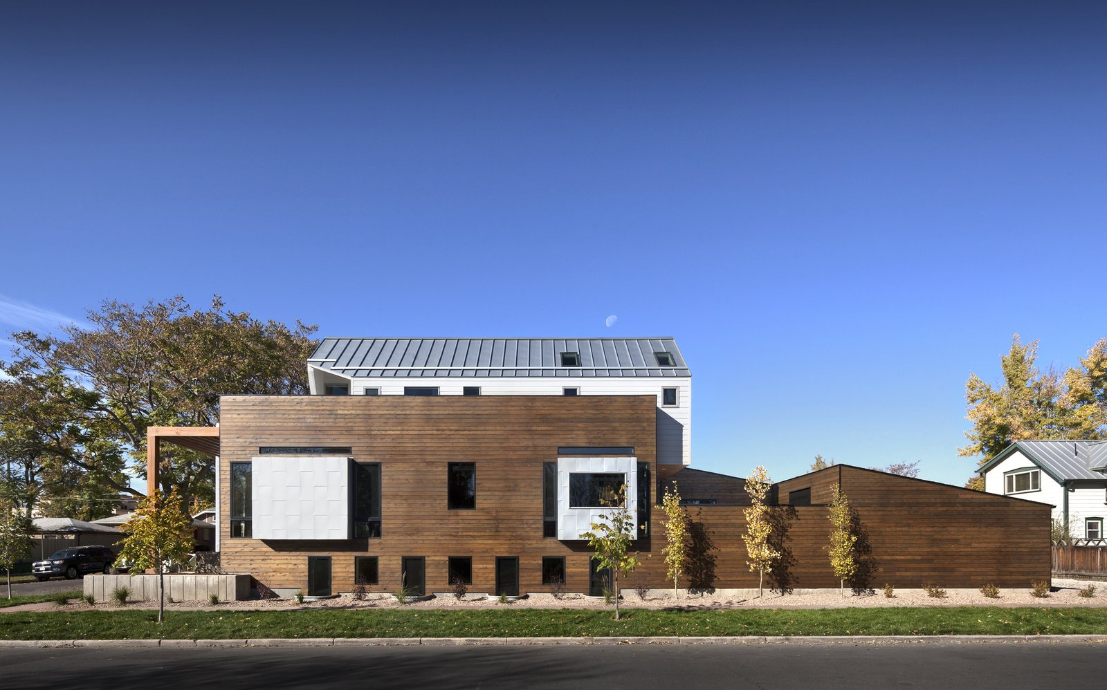 """Considering all of the foot traffic around their property, [the owners] made it very clear that they wanted to find a way to maintain as much privacy in the home as possible,"" architect Chad Mitchell says of this Denver home. ""Thus, the main floor of the home is elevated from the sidewalk by about six feet."" The exterior siding is red cedar with a custom Sherwin-Williams stain. Tagged: Exterior, House, Wood Siding Material, Metal Siding Material, and Metal Roof Material.  Modern Homes in Colorado by Luke Hopping from Highlands House"