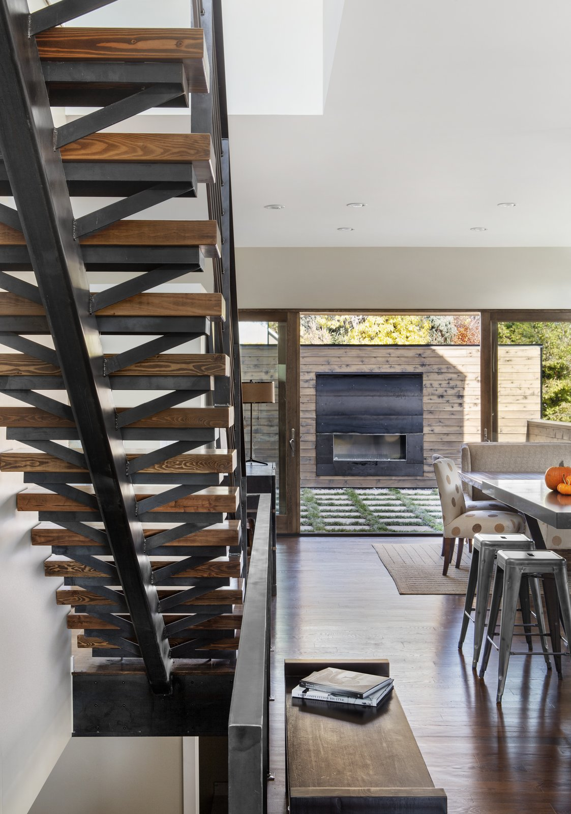 "Mitchell wanted to detail the solid oak staircase with that same sense of openness, even though its materials are heavy. ""We used a lot of raw steel and wood on the interior of the home,"" Mitchell said. ""This carries the authenticity of real materials from the building exterior to the building interior."" A custom fireplace sits on the patio."
