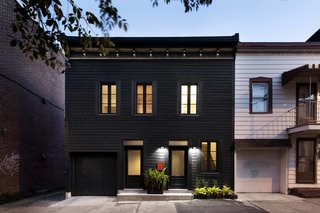 15 Modern Homes with Black Exteriors - Photo 15 of 15 - The owners' goal was to transform the 19th-century building into a bold single-family residence. Historical architectural details were made modern with a striking black facade, while inside, a flexible living space that opens into an exterior garden enables a simplified lifestyle.