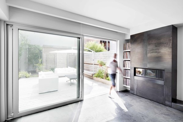A 13-foot-wide sliding door by Portes Unis St-Michel opens the rear exterior onto a terrace, where the owners spend much of their time. The Series Skyline fireplace by Marquis and movable furniture make the garden an extension of the living space in all seasons.
