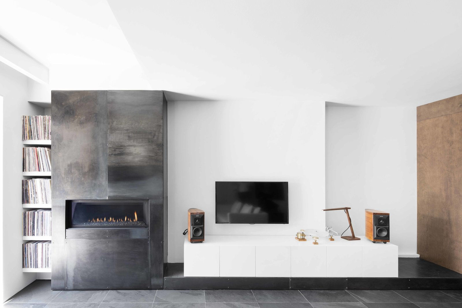 The communication between interior and exterior is unmistakable. The polished steel that surrounds the fireplace and the concrete floor's dark finish recall the home's exterior, while the contrasting stark white walls create a visual language as striking as the building's black facade. Tagged: Living Room, Gas Burning Fireplace, and Slate Floor.  Photo 3 of 7 in A Monochromatic Renovation for a 19th-Century Montreal Home