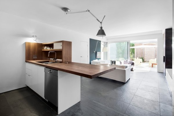 By foregoing a fixed dining table in favor of a large American walnut wood countertop by Cuisine Elysee, the couple is able to enjoy a open space with a clear view of the back of the house and the garden terrace outside.