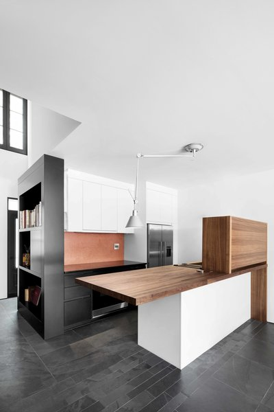 A short wall on the kitchen island hides clutter and keeps the straight lines of the design unmarred. Almost every lighting fixture, including the overhead Artemide Tolomeo light, is movable. The refrigerator and oven are from Fisher and Paykel.