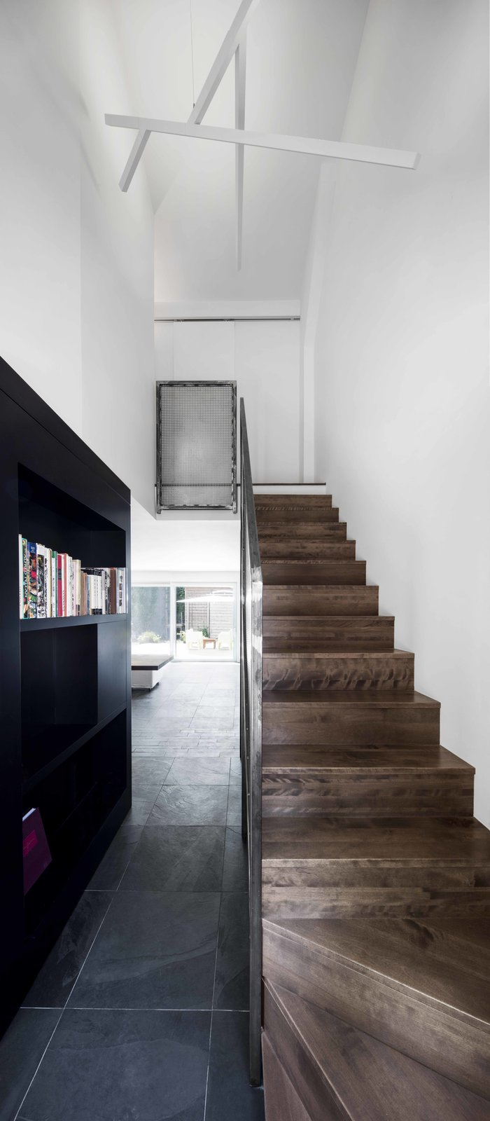 The staircase's steel guardrail and the custom black bookshelf create a link between the kitchen, the living space, and the entryway. Tagged: Staircase, Wood Tread, and Metal Railing.  Best Photos from A Monochromatic Renovation for a 19th-Century Montreal Home
