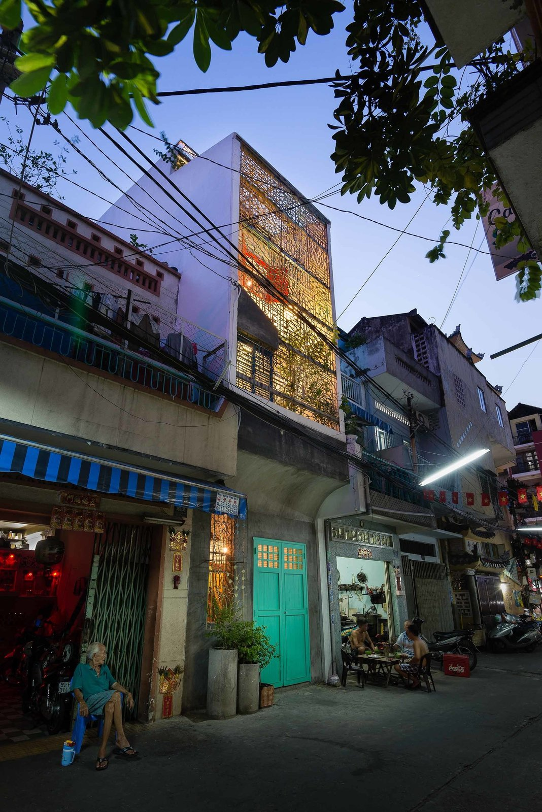 A patterned steel frame serves as a front wall to the street, allowing for light and noise to penetrate the interior. The owners were adamant about the importance of integrating the culture and traditions of Saigon into their home, hoping their children would grow up with a knowledge of and appreciation for the city. Tagged: Exterior, House, and Concrete Siding Material.  Photo 1 of 10 in A Narrow Courtyard Joins a Unique Two-Family Home in Saigon