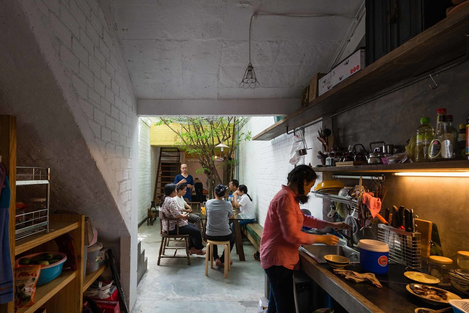 The alleyway extends into a full kitchen, where meals can be prepared right beside family gatherings. While the main frame of the home was built with the typical concrete, brick, and steel, the materials for the roof and floor tiles, as well as doors, windows, shelving and interior furnishings, were sourced primarily from demolished Saigon homes.  Kitchen by Lp from A Narrow Courtyard Joins a Unique Two-Family Home in Saigon