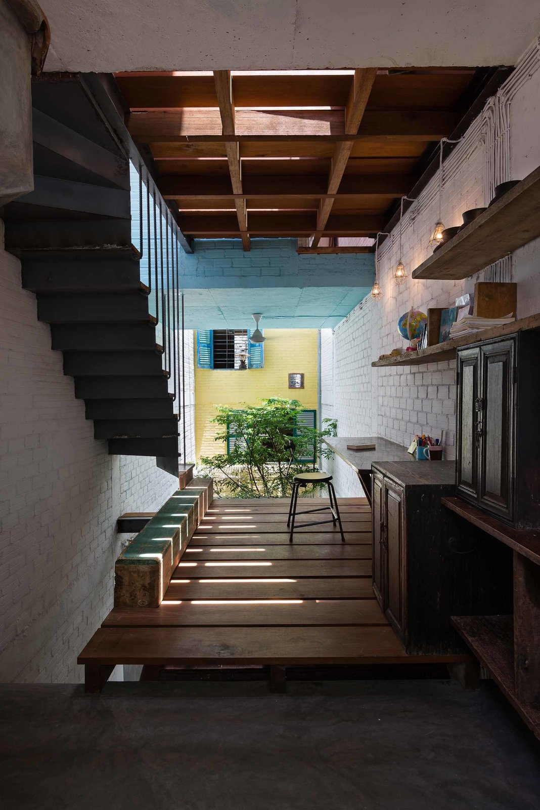 A rare interior hallway space is made and furnished almost entirely with reclaimed materials. Materials for doors, windows, and the slatted wooden floor were collected from demolished Saigon homes and customized to fit the residence.  Photo 7 of 10 in A Narrow Courtyard Joins a Unique Two-Family Home in Saigon