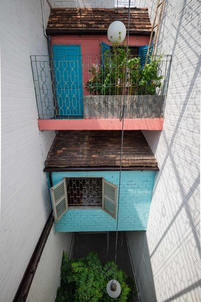 Flowering balconies are common in Saigon, where residents can interact with the city outside. Here, a beautifully patterned steel frame contains a cantilevered internal balcony, which looks out over the outdoor dining area's net ceiling.
