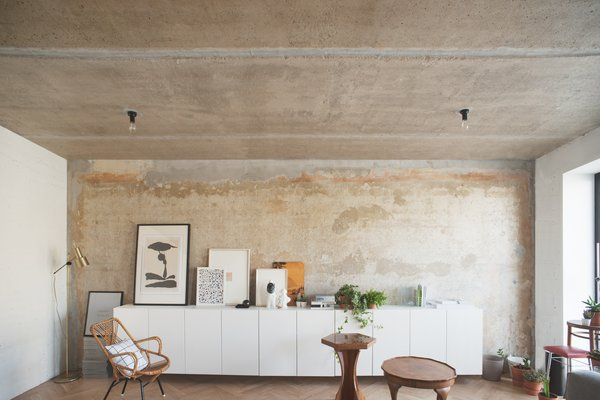 """Crosby Studios eventually found this rust-washed concrete wall underneath many layers of wallpaper. """"Nobody even thought to paint it,"""" explains Dmitry. """"The ceiling was polished until it was concrete, and then covered in laquer."""" Photo  of Soviet Intelligentsia modern home"""