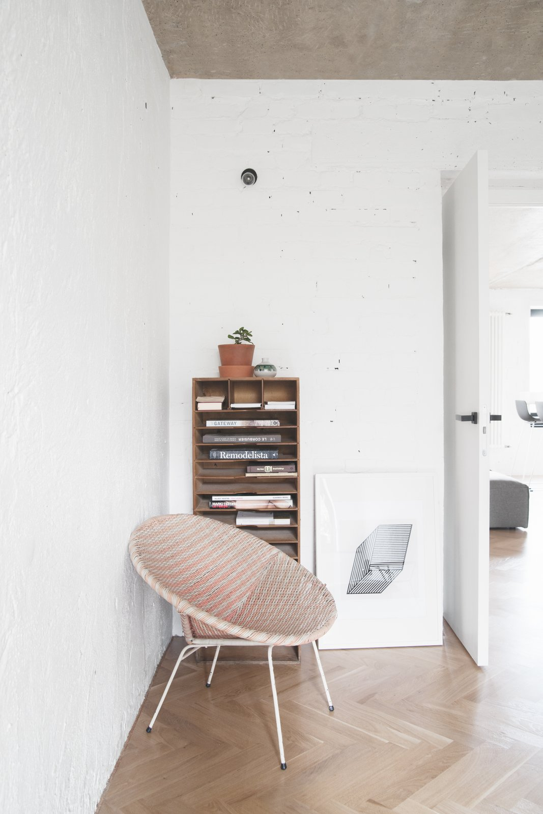 No space is wasted in the apartment—even behind-the-door corners. A statement bowl chair from the 60s, bought at an English flea market, makes for a stylish reading nook.  Soviet Intelligentsia by Caroline Wallis