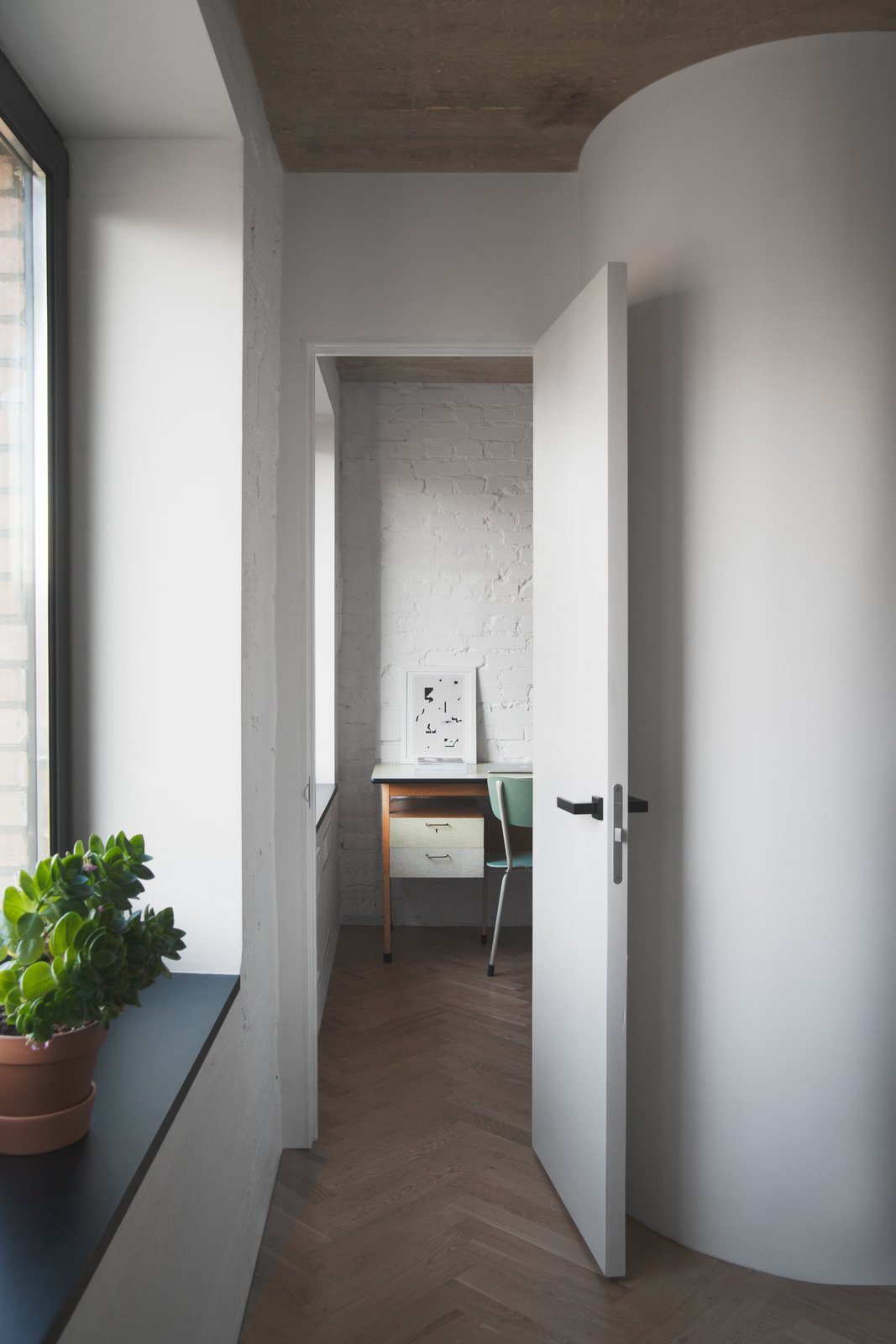 "To make the most out of a small footprint, Vorontsov experimented with some creative partitions. He explains how ""the partitions we built were straight, and then we rounded the corners slightly in the studio"" to create a little extra room. ""We left the doors without architraves, and punctuated the detail with black doorknobs."""