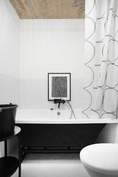 The approximately 4 inch by 4 inch white ceramic tile flooring is typical of Soviet-era bathrooms. Vorontsov sought to update the utilitarian style of the original bathroom with Kludi Bozz fixtures (which he painted black himself) and a graphic IKEA shower curtain. Photo 8 of Soviet Intelligentsia modern home