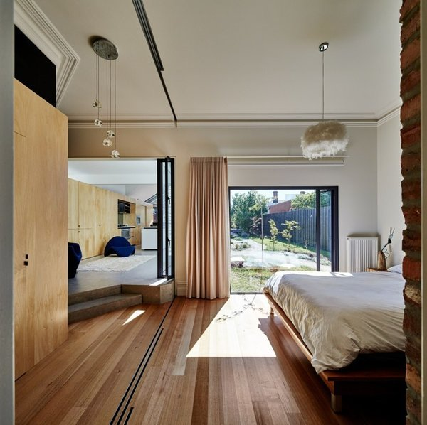 Three plywood veneer sliding doors separate the bedroom from the hallway. Photo 7 of Cut Cut Paw Paw modern home