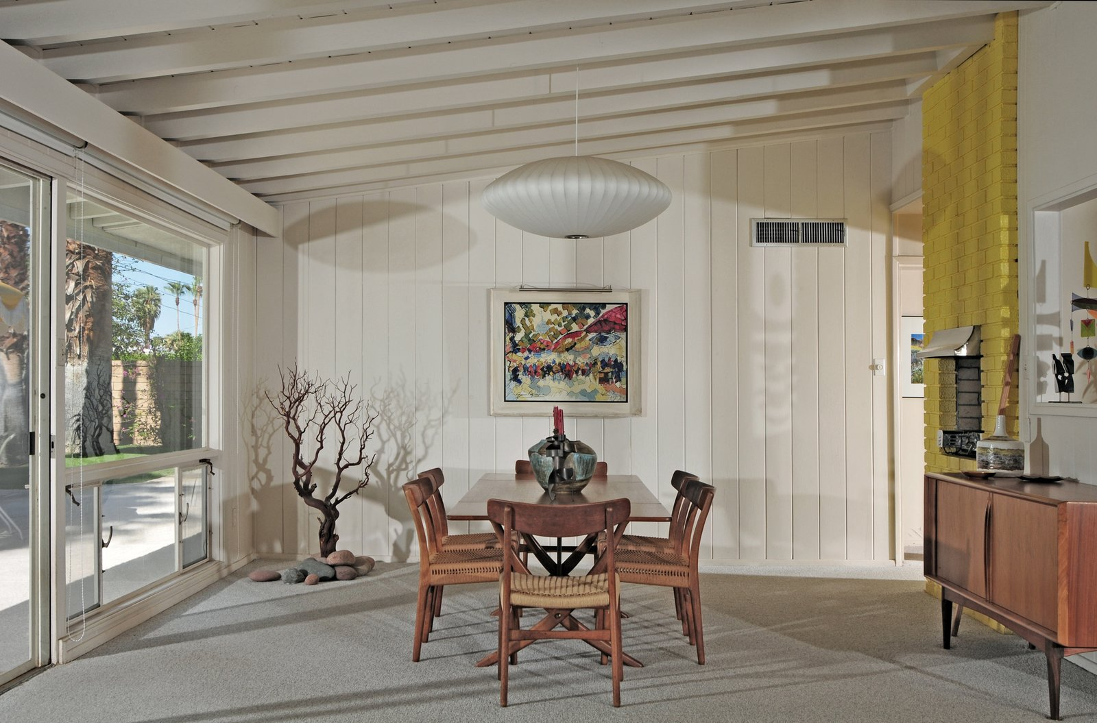 The 1956 LeBaron-Moruzzi Residence by Sam Pascal features all-white interiors with vibrant yellow accents, as seen with the chimney at right. Tagged: Dining Room, Chair, and Table.  Midcentury Homes by Dwell from A New Book Documents the Rarely-Seen Midcentury Modern Gems of Palm Springs