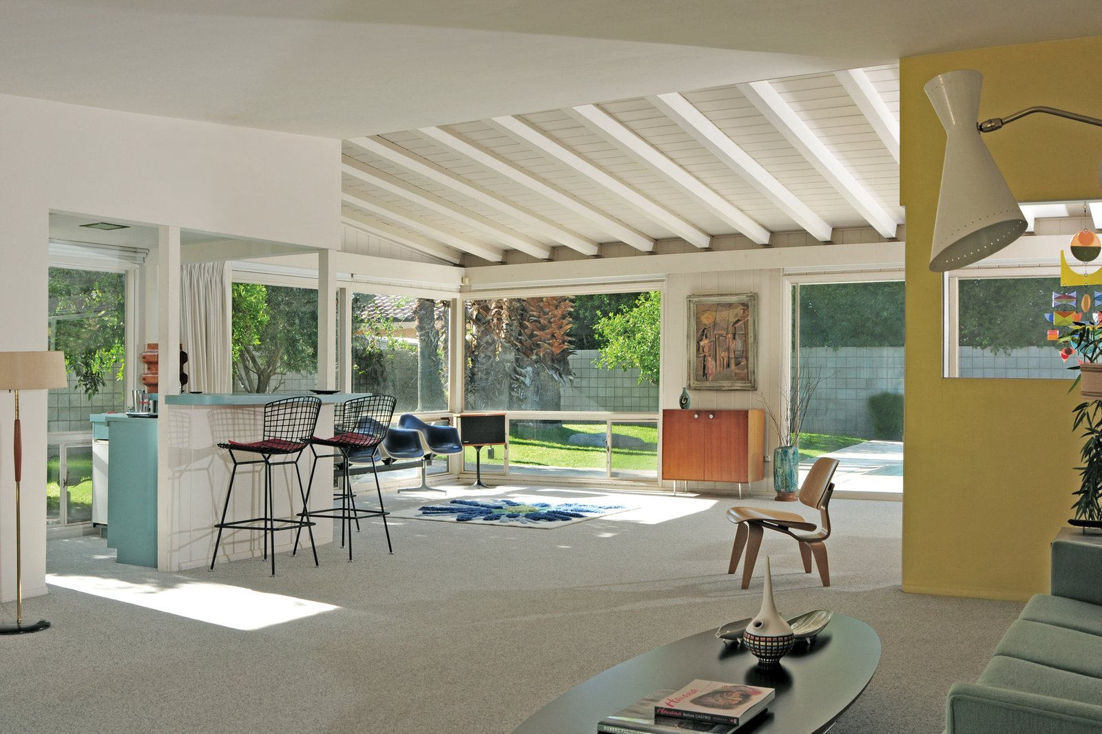 Its living room features an Eames LCW, Bertoia Barstools, and Eames Tandem Shell Seats. Midcentury Homes by Dwell