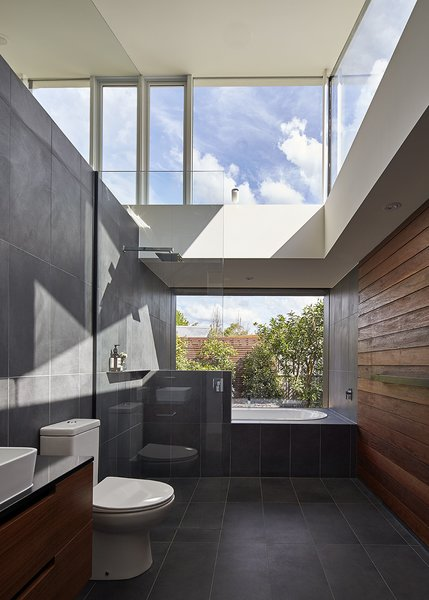 An Envy II Wall-Faced Suite toilet by Parisi sits in the home's sole bathroom and Caroma's Starlett 1850 Island Bath was installed next to the window. Photo 7 of Breeze modern home