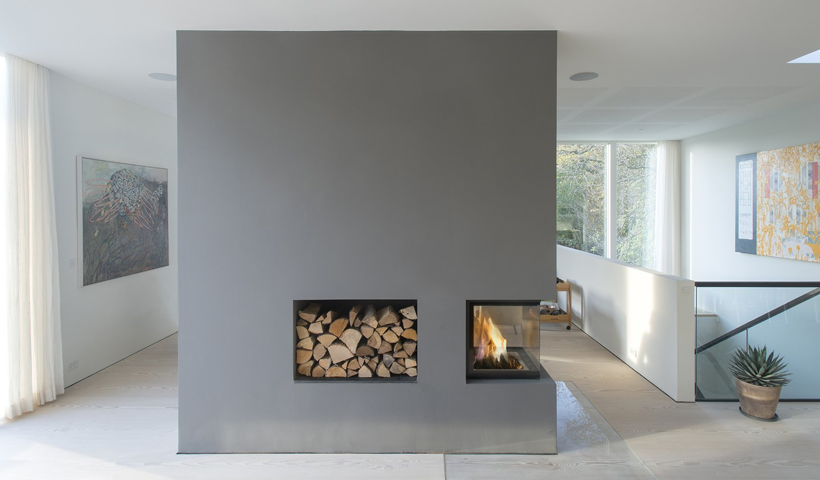 A three-sided fireplace offers warmth.  97+ Modern Fireplace Ideas by Dwell from Villa R