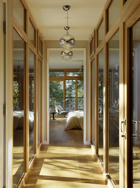 A bridge connects the second-floor office and guest bedroom with the backyard-facing master bedroom. To prevent excessive solar heat gain in this especial space, Butler Armsden used high performance Unilux low-e windows. Two Eurofase pendant lights from Chromos illuminate the hallway at night.