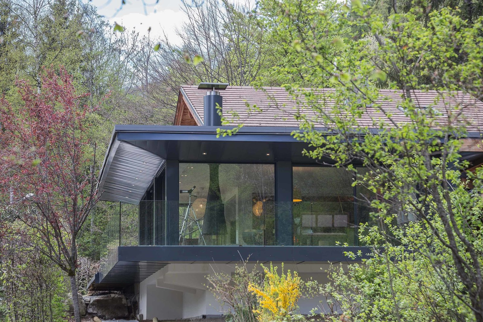 A natural rock face supports the cantilevered addition from below, creating a fortress-like structure that sits lightly within the existing landscape. Neutral colors keep the home from standing out, while the glass reflects surrounding flora.