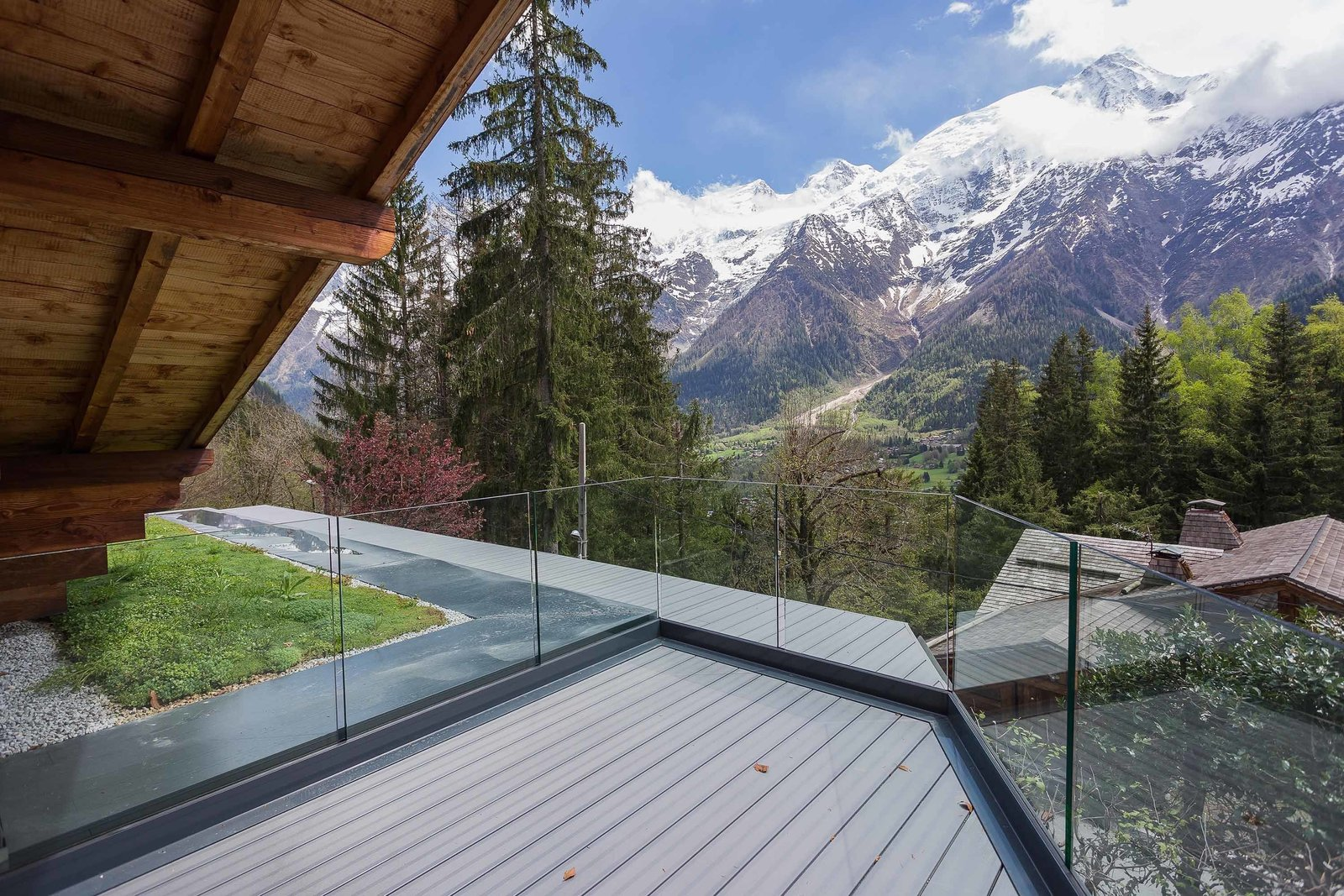 Glass walls fence in an outdoor deck without obstructing spectacular views of the mountains and valley.  Photo 5 of 8 in A Mountain Hideaway Plants a Green Roof in the French Alps