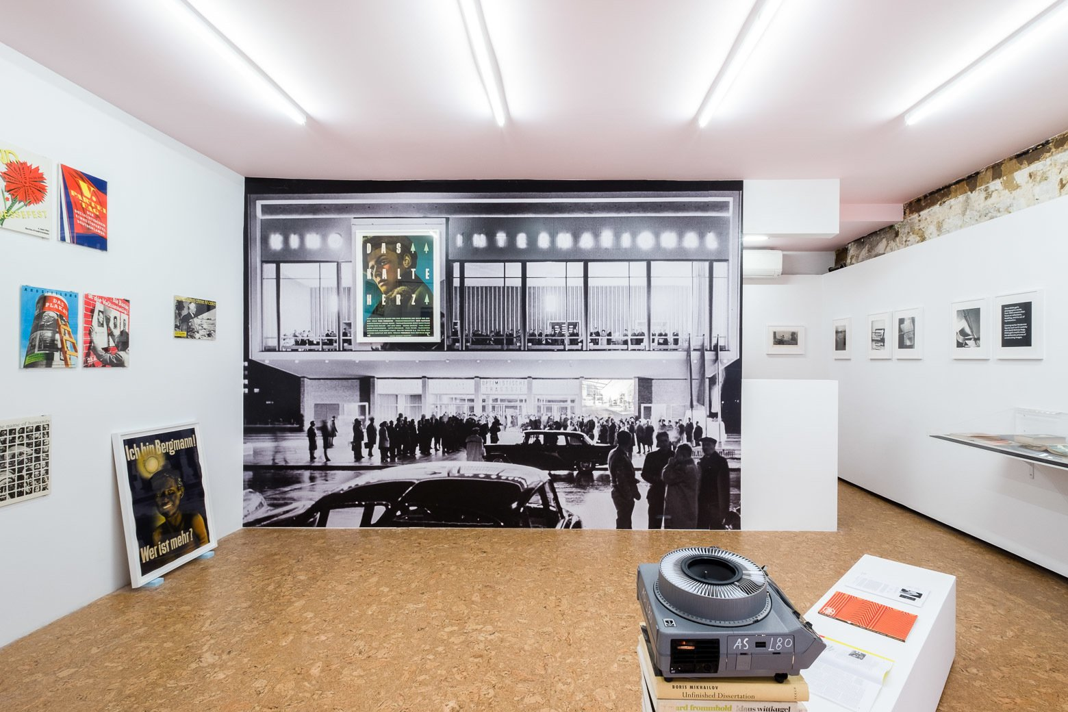 """This view captures the main installation gesture of the exhibition and also what's visible from street level. In his exhibition designs, Klaus Wittkugel often used large-scale panoramas of the city to transport the viewer into another context,"" notes Krishnamurthy. ""Here, I'm turning this display strategy back onto Wittkugel himself. This is an image of Kino International, a modern film theater in East Berlin from 1963. For this architectural icon, Wittkugel designed the signage, including a clever spot to hang a poster as the 'space' in the name of the building. Here, I've blown up a historical image of the façade to room-sized proportions and gone one step further: one of Wittkugel's most striking posters, Das Kalte Herz [The Cold Heart], 1950, hangs framed on top of the building. An analogue slide projector plays a loop of selected images from Wittkugel's exhibition designs, retrospective exhibitions, and architectural commissions, interspersed with contemporary images of those same locations and screenshots of the digital models of my exhibition design that mirror these historical views. Installed as if the spectators out front are watching the projection, this display is the centerpiece of the show.""  Photo 5 of 6 in A Look at Klaus Wittkugel, East Germany's Most Prolific Graphic Designer"
