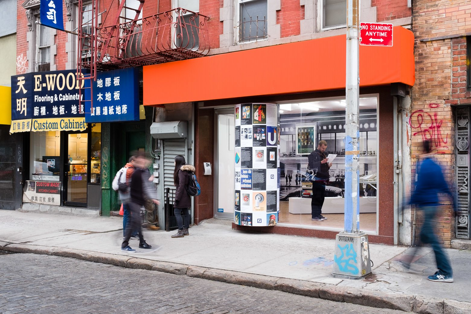 """As part of the exhibition display, Krishnamurthy installed a large poster column that protrudes from the gallery's storefront facade. """"Klaus Wittkugel believed in the street as a primary context for graphic design: a large portion of his work consisted of posters, meant to catch your eye while walking. As P! is in Chinatown and has a very public presence, I decided to extend this gesture and make it a key feature of the exhibition,"""" he says. """"In Berlin, you still see a lot of Littfasssäulen, a distinctive and typical kind of poster column. Together with Cay Sophie Rabinowitz, curator of the parallel exhibition on Anton Stankowski at OSMOS, I conceived an installation that would display reproductions of work by the two Cold War designers together. There is also a second poster column at OSMOS, which is the 'umbilical cord' between these two otherwise independent exhibitions. The installation echoes Wittkugel's own approach to his retrospective exhibition in 1961, when he covered the poster columns in the city with a selection of his past work, along with the posters announcing the show. Artist Maayan Strauss had the brilliant idea of making the poster column 'break out; of the gallery, so that it seems to literally cross over a border. Wittkugel's first job was as a window-dresser, so it's an appropriate homage to have this kind of attention paid to the storefront window."""""""