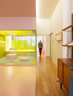 A Creative Dreamworld Complete With Neon Rooms and a Tropical Garden - Photo 3 of 11 - In the upstairs apartment, glass partitions keep the elongated loft open and spacious, while lighting is placed against brightly colored walls to create a cool, atmospheric glow.