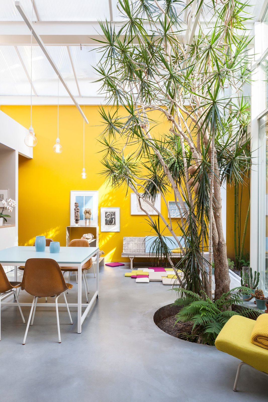 Furnished with vintage Eames chairs, a second-hand sofa, and pendants and tables designed by Nathalie, the space is kept purposefully casual. She painstakingly mixed and tested the paint for the mustard-yellow walls herself—15 times—to match the hue of a Kvadrat textile.  Photo 7 of 12 in A Creative Dreamworld Complete With Neon Rooms and a Tropical Garden