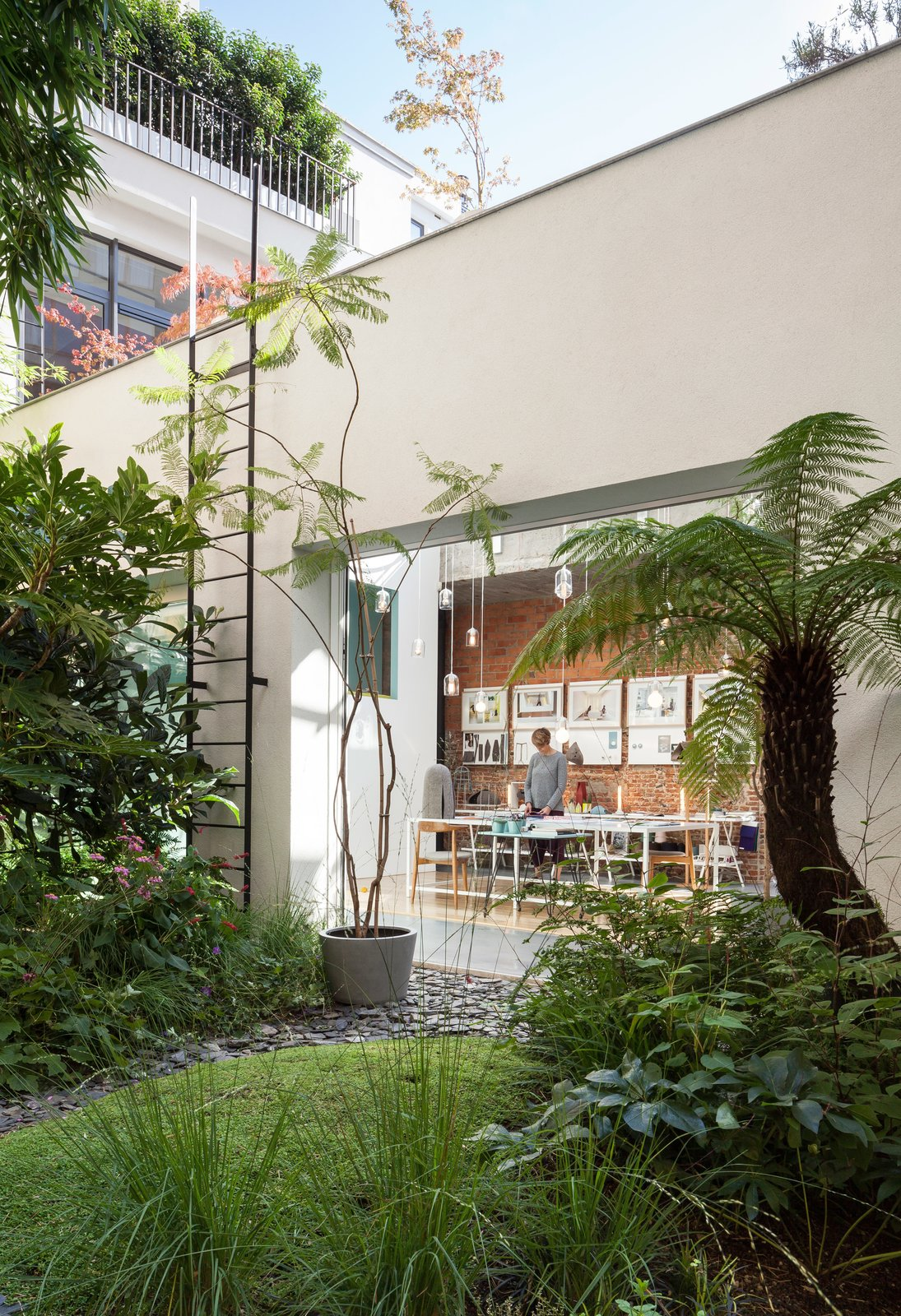 She also designed the table, surrounded by vintage Wishbone chairs by Hans Wegner, in her studio. Tagged: Outdoor, Grass, and Back Yard.  Photo 6 of 12 in A Creative Dreamworld Complete With Neon Rooms and a Tropical Garden