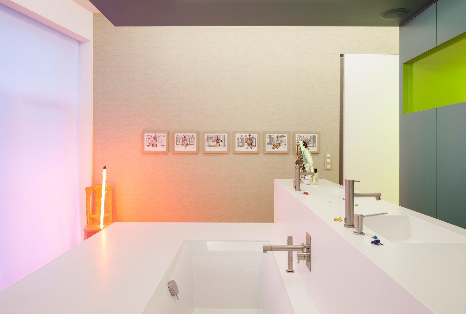 Installed by a local vendor, the Corian sinks and bath combine to form a freestanding island in the upstairs bathroom, outfitted with fixtures by Ritmonio. A series of artworks by Tim, including a sculpture that emits a soft glow, accent the pristine space. Tagged: Bath Room, Alcove Tub, and Undermount Sink.  Photo 8 of 12 in A Creative Dreamworld Complete With Neon Rooms and a Tropical Garden
