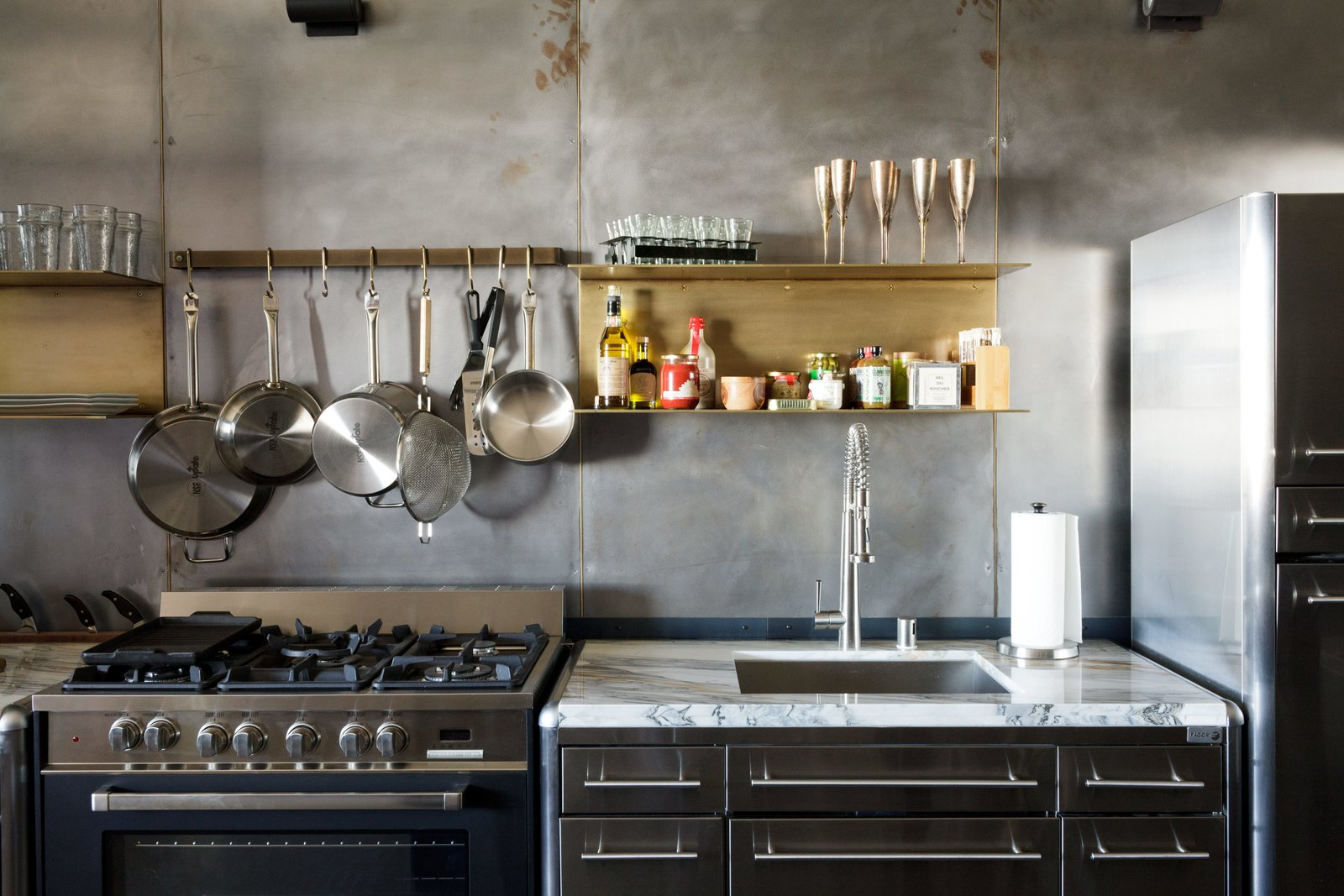 Floating brass shelves fabricated by local sculptor Gilad Ben-Artzi contrast the steel wall.  Photo 4 of 6 in Steel and Brass Cover Nearly Every Surface of this Industrial L.A. Kitchen