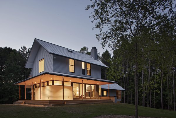 """""""The main volume presents a traditional front and is wrapped on the west and south by a deep porch,"""" says architect Erin Sterling Lewis. """"Living and dining spaces access the porch."""" A standing seam metal roof with a Kynar finish and HardiePlank Lap Siding cover the exterior of this 3,000-square-foot home. Photo  of The Farmhouse modern home"""