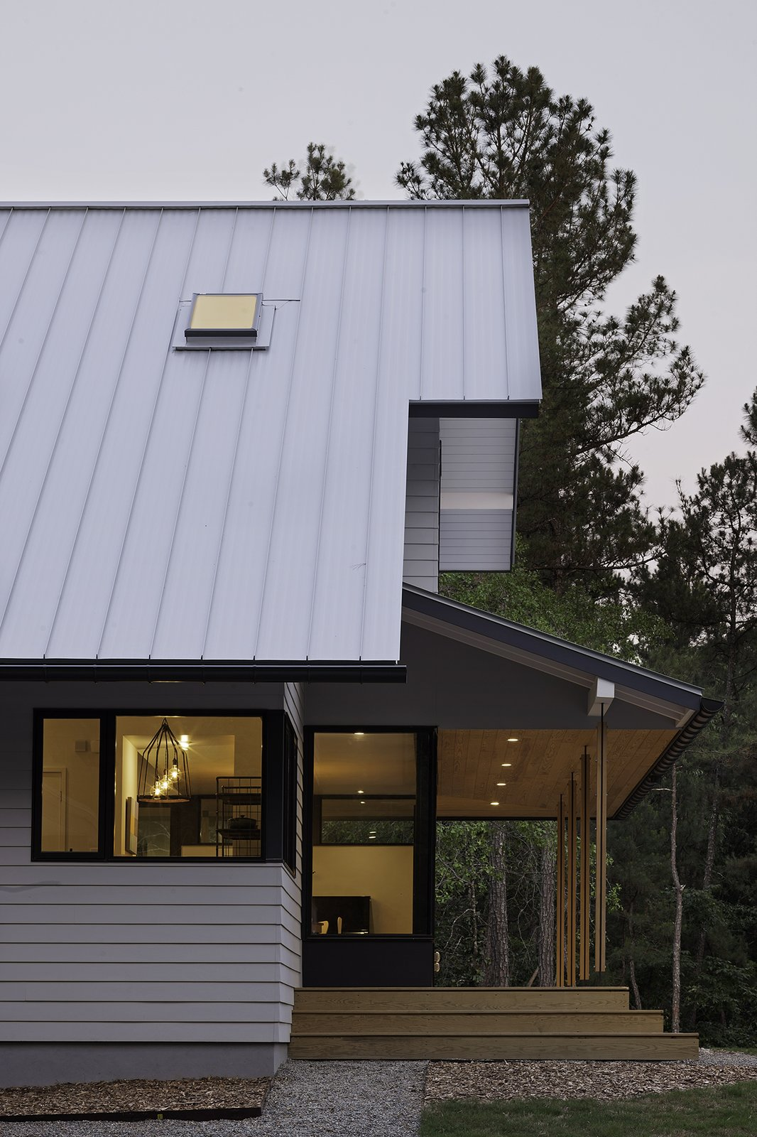 """Our goal was to strike a good balance between traditional and modern in a way that did not result in simply a traditional exterior and modern interior,"" says Lewis. A pressure-treated wood deck extends from the property under a stained pine, V-groove ceiling. Steel and wood comprise the columns. Tagged: Exterior, Metal Roof Material, House, and Gable RoofLine.  The Farmhouse by Kelly Dawson"