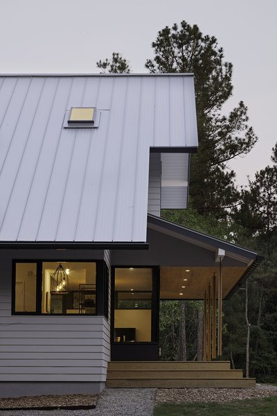 """""""Our goal was to strike a good balance between traditional and modern in a way that did not result in simply a traditional exterior and modern interior,"""" says Lewis. A pressure-treated wood deck extends from the property under a stained pine, V-groove ceiling. Steel and wood comprise the columns. Photo 3 of The Farmhouse modern home"""